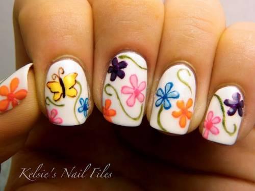 unha decorada com borboleta e flores coloridas